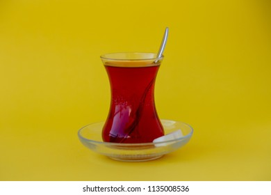 Glass of Turkish tea with sugar cubes on yellow background