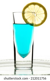 Glass with turquoise drink and lemon in the backlight