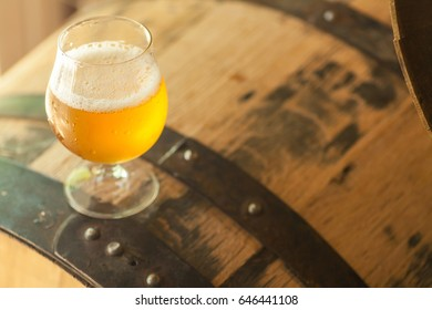 Glass of unfiltered light beer standing on an oak wood barrel in a brewery