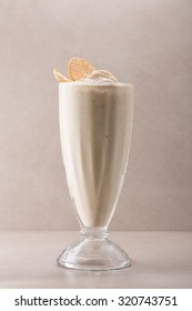 Glass of vanilla milkshake isolated on grey background