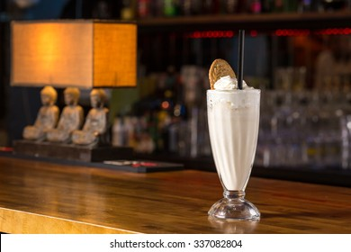 Glass of vanilla milkshake on bar counter