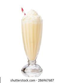 Glass of vanilla milkshake with whipped cream isolated on white background