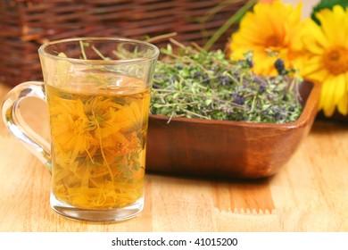 Glass of various infused herbs and bowl with dried thyme
