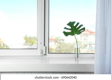 Glass vase with beautiful tropical leaf on window sill