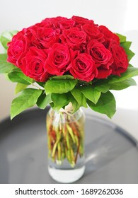Glass vase with bouquet of beautiful red roses on white background on the table.