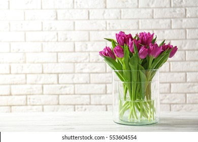 Glass vase with bouquet of beautiful tulips on brick wall background