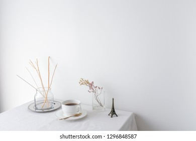 Glass vase of dried flower plant an eiffel tower miniature on white table top on white wall background with blank copy space for product mock up placement