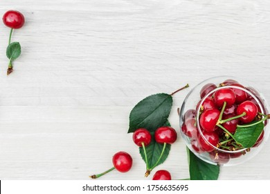 Glass vase in the form of a bowl with ripe cherries stands on a white wooden background. Scattered berries and cherry leaves on a wooden white background. Wooden background, cherries with free space