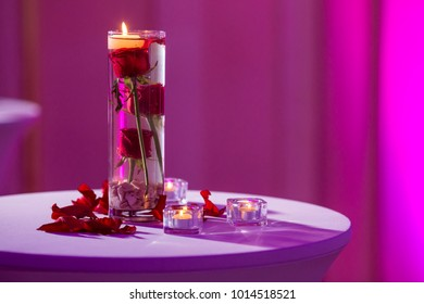 Glass vase with red roses water and light candles