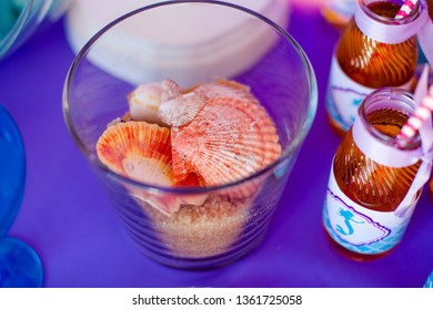 Glass vase with sweet brown sugar sand and difftent seashells. Seatime theme on the party's candybar.