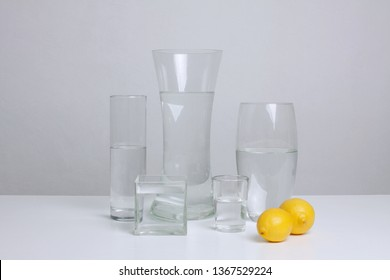 Glass vases with water and lemons. Minimalistic still life.