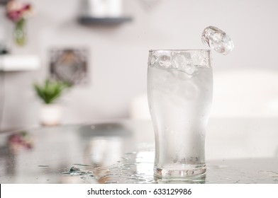 Glass of very cold water and ice on table
