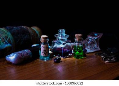 Glass vials and bottles with various potions and poisons for conducting a mystical ritual. Multi-colored potions next to coins on a wooden table in a dark room