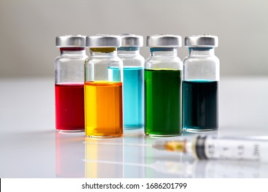 Glass vials with colored medicine liquid and syringe. White reflective surface.