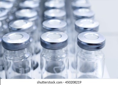Glass vials for liquid samples. Laboratory equipment for dispensing fluid samples. Shallow depth of field.