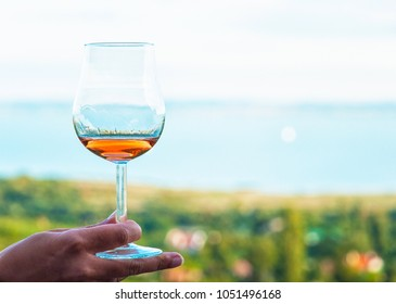 Glass of vine with lake Balaton in the background