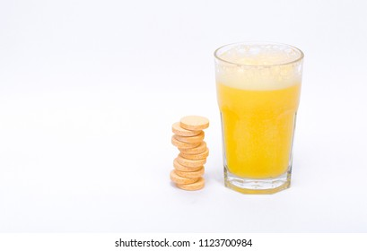 A glass of vitamin orange juice cool on a white background effervescent tablets vitamins
