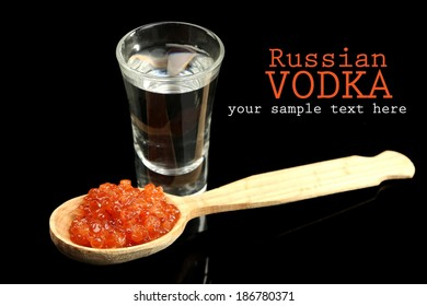 Glass of vodka, red caviar  isolated on black