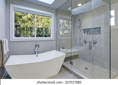 Glass walk-in shower with gray subway tiled surround and white freestanding tub in new luxury home bathroom. Northwest, USA