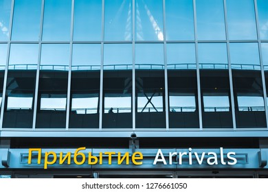 """Glass wall Pulkovo airport in St. Petersburg with the inscription """"Arrivals"""" in two languages - in Russian and English."""