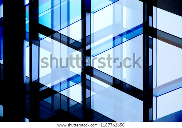 Glaswand mit Stahl- oder Aluminiumrahmen. Strukturverglasung. Nahaufnahme eines Bürogebäudefragments im Schatten gegen klaren blauen Himmel neu aufbereitet. Abstrakter, moderner Architektur-Hintergrund.