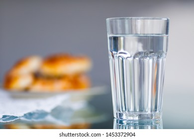 A glass of water and blurred cakes in the background