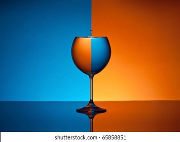 Glass of water with drop and colored background