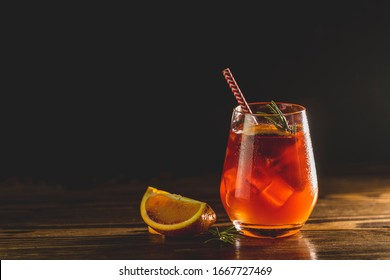 Glass with water drops of Italian aperol spritz cocktail with orange slices, ice and minton dark wooden table with amazing back light Milano spritzer alcoholic cocktail with red bitter, dry white win