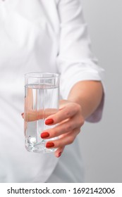 Glass of water in female hand of doctor on white background close up.