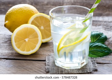 Glass of water with fresh lemon juice on the wooden table