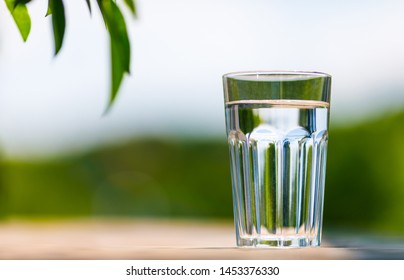 A glass of water with green blurred background