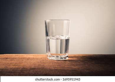 Glass of water with half full water on the table, concept of positive and negative thinking