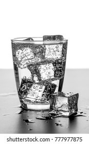 A glass of water and ice cubes on a wet surface with copy space