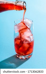 Glass of water with ice cubes and strawberry syrup. Pouring syrup from a glass bottle to a glass full of ice cubes. Drink preparation in bright light on a blue colored background