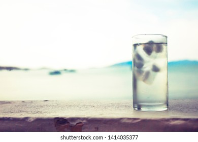 glass of water with ice on the beach sand at hot summer day