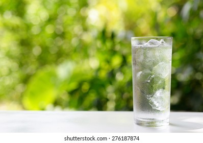 a glass of water with ice on nature background.