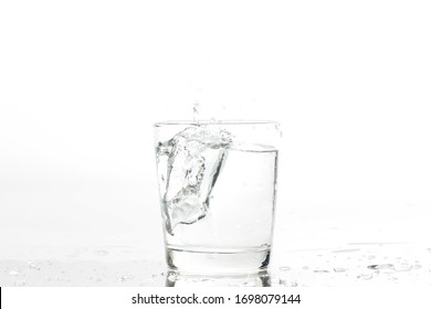 Glass with water and ice on a white background. Glass of mineral water and ice on white background.