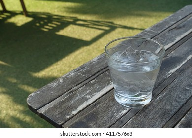Glass of water with ice on the wooden table in the garden in a very hot day.