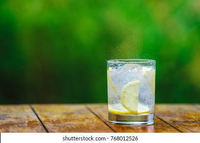 A glass of water. Lemon. Cocktail straw. A green background Mineral water