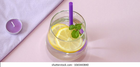 Glass of water, lemon and mint, and candle. Glass of pure water, fresh organic lemon and mint isolated on purple background. Detox and healthy food concept. Boost your metabolism concept. Aromatherapy