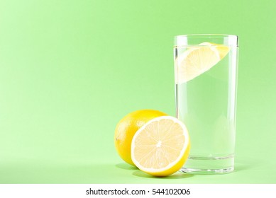 glass of water with lemon on a green background