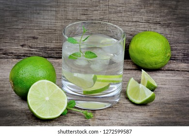 Glass with water and lime on wooden table