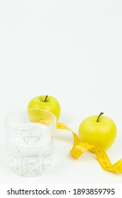A glass of water and a measuring tape wrapped around two green apples as a symbol of diet. The concept of a healthy lifestyle, food and sports, on a white background. Side view with place for text or