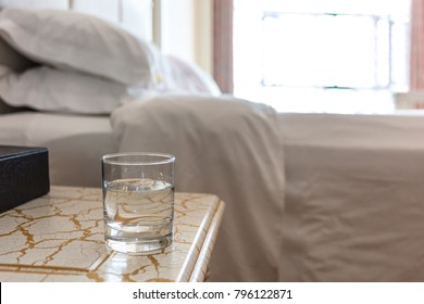 A glass of water on the bedside in the hotel room