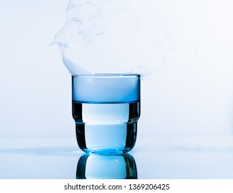 Glass of water on a blue background. Water  into glass on   smoky background