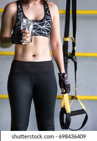 Glass of water on hand with nail paint of sport woman, woman on sport bra with TRX