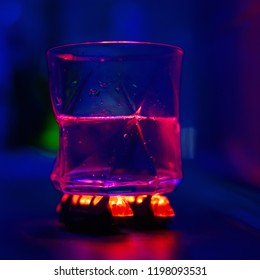 a glass with water on a red led lights on a blue background