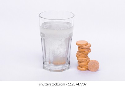 Glass with water on a white background with effervescent tablets vitamins