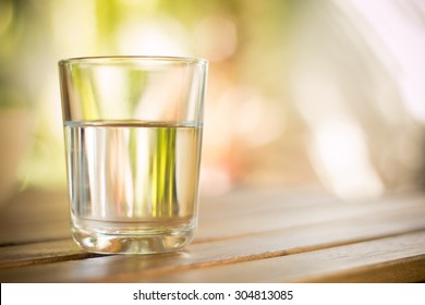 glass of water on wooden table bokeh background - vintage style picture