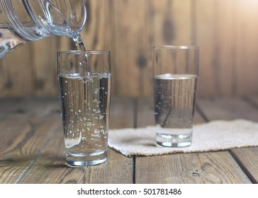 Glass of water on a wooden table. Water was poured into the beaker. Selective focus. Shallow DOF. With lighting effects.
